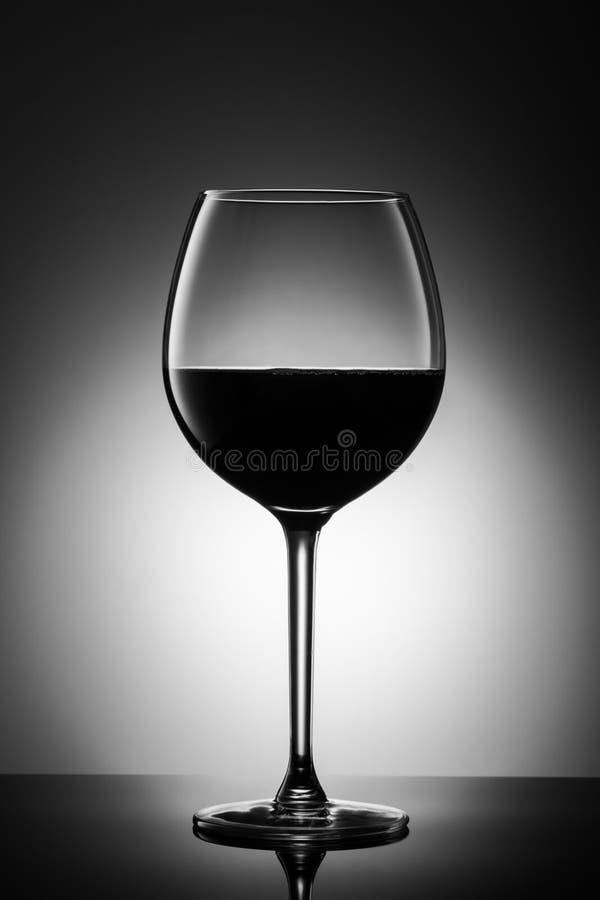 Stor glass rött vinform av mörker från druvaalkoholdrycken på lysande bakgrundsadvertizingskott royaltyfri bild