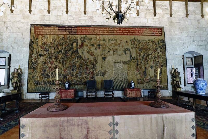 Stor gobeläng som broderas på väggen av ett av rummen av slotten av hertigarna av Braganza med en tabell med candelabr två royaltyfri bild