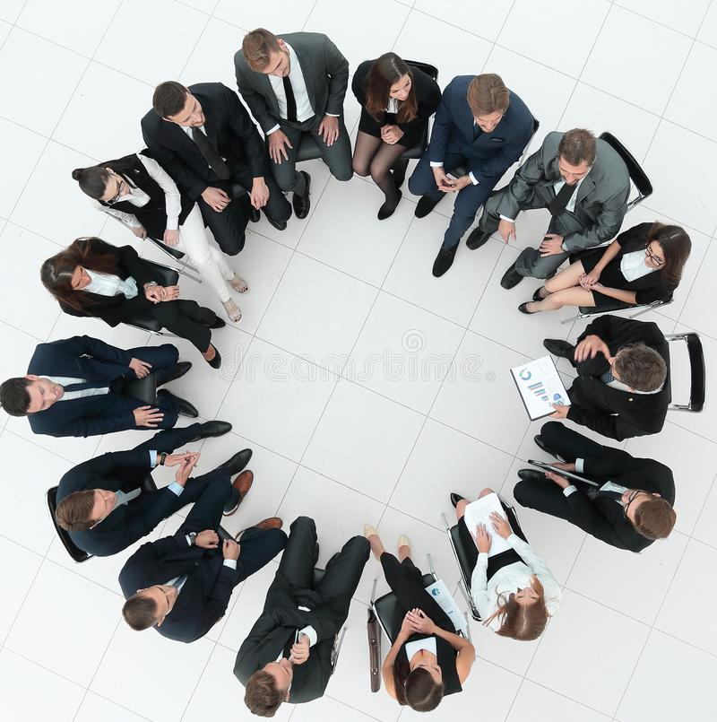 Stor grupp av affärsfolk som sitter på ett affärsmöte arkivbild