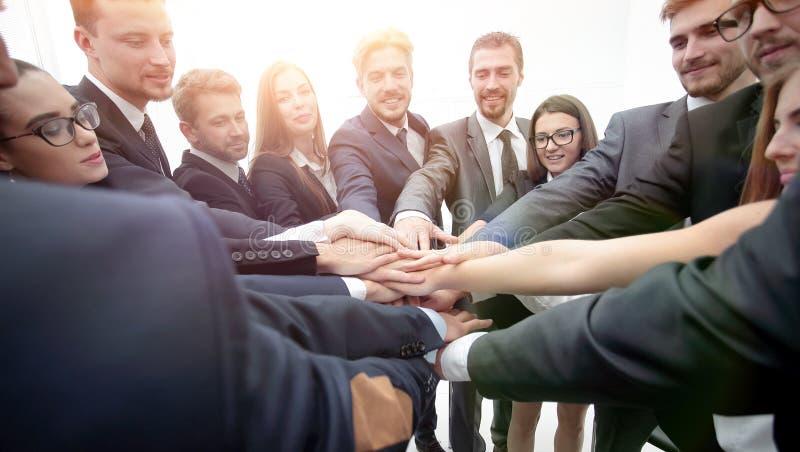 Stor grupp av affärsfolk som står med vikt handtogeth fotografering för bildbyråer