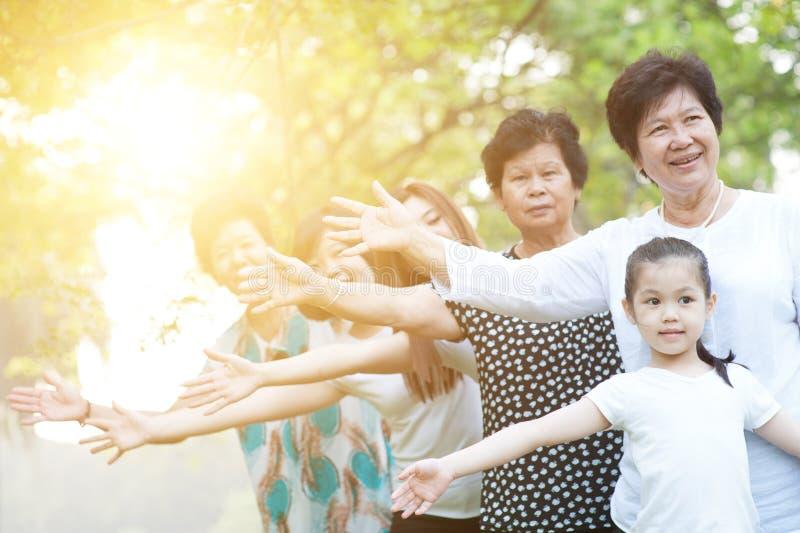 Stor grupp av den asiatiska mång- utvecklingsfamiljen som utomhus spelar fotografering för bildbyråer