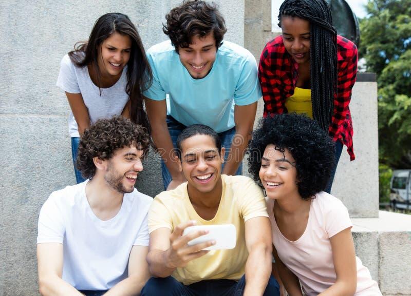 Stor grupp av internationellt ungt vuxet folk som ser mobil arkivbild