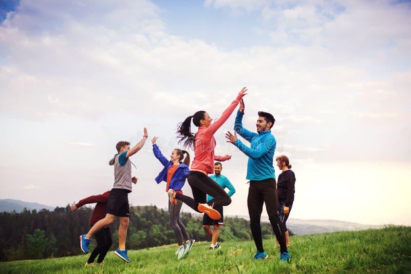 Stor grupp av passformen och aktivt folk som hoppar, når att ha gjort övning i natur arkivfoton