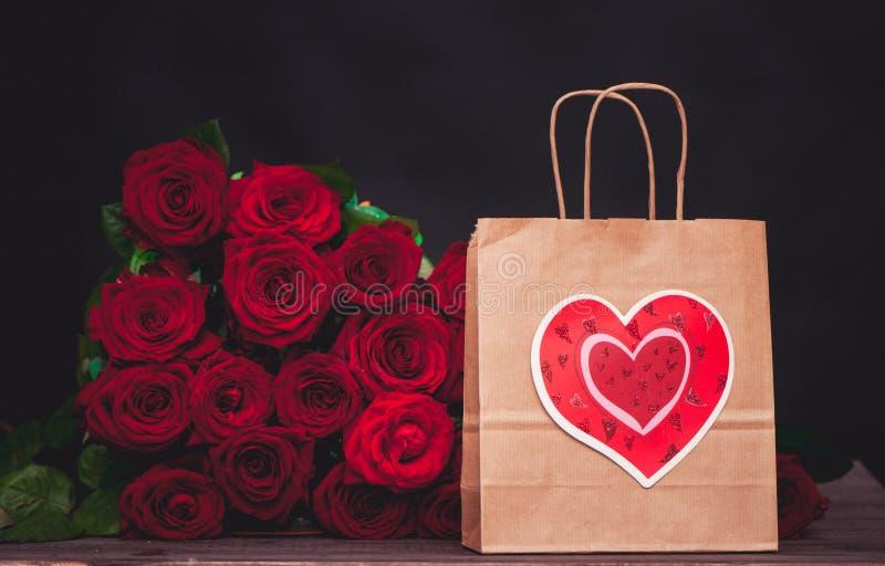 Stor grupp av röda rosor och en gåvapåse med en hjärta fotografering för bildbyråer