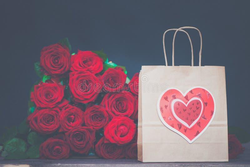 Stor grupp av röda rosor och en gåvapåse med en hjärta Begreppet av en gåva för valentin dag, förälskelse, bröllop arkivfoto