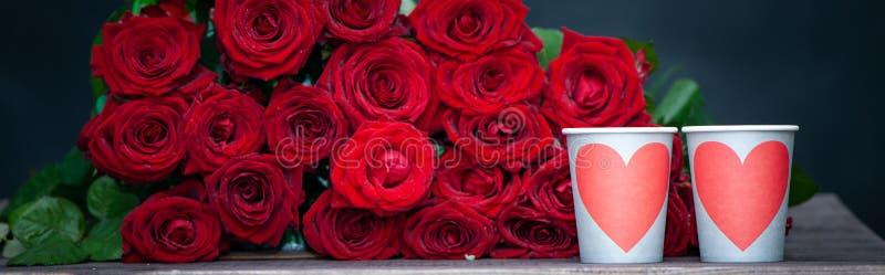 Stor grupp av röda rosor och två koppar med hjärtor arkivbild