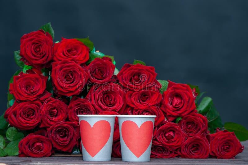 Stor grupp av röda rosor och två koppar med hjärtor arkivbilder