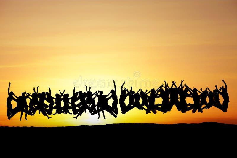 Stor grupp av tonår som hoppar i solnedgång royaltyfria foton