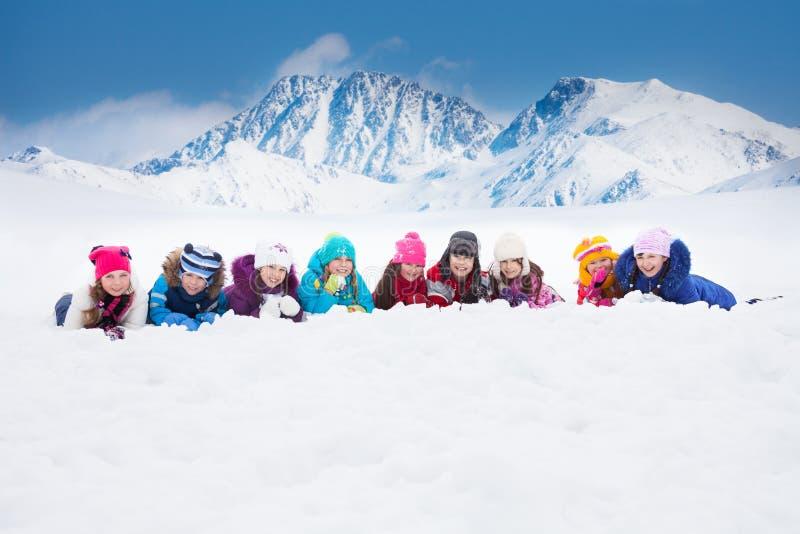 Stor grupp av ungar som lägger i snö royaltyfri fotografi