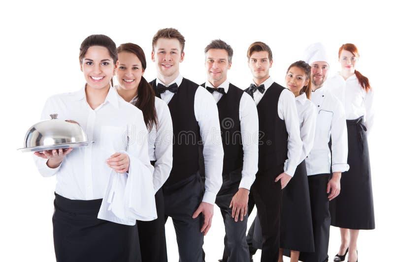 Stor grupp av uppassare och servitriers som står i rad royaltyfri bild