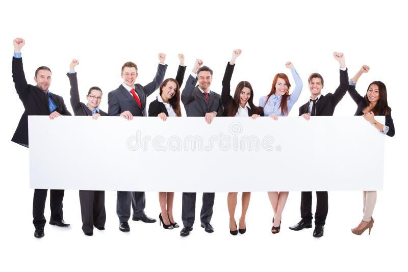 Stor grupp av upphetsade businesspeople som framlägger banret royaltyfri bild