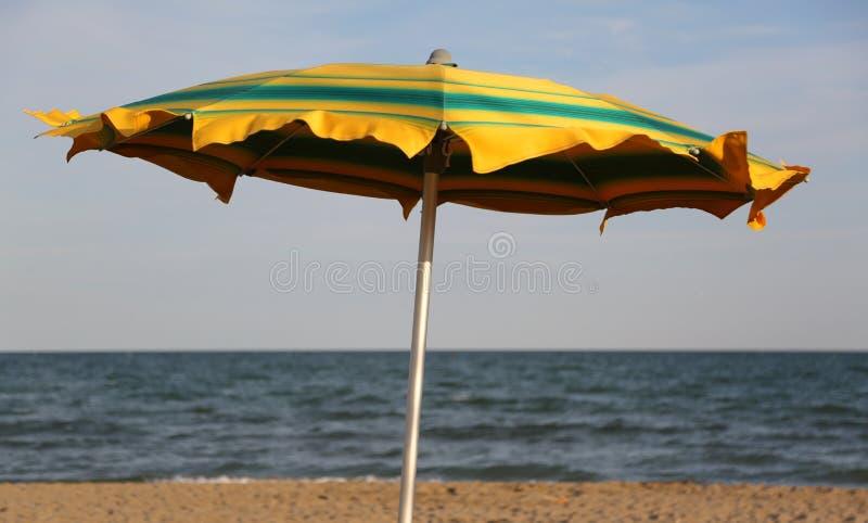 stor gul och grön slags solskydd på stranden och havet på backgro royaltyfria foton