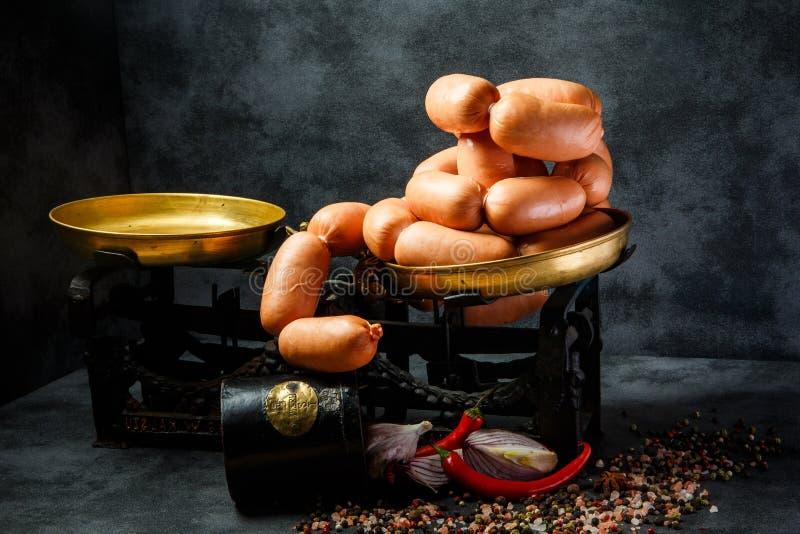 Stor hög av korta tjocka frankfurterkorvar i spiral med löken och chili royaltyfri foto