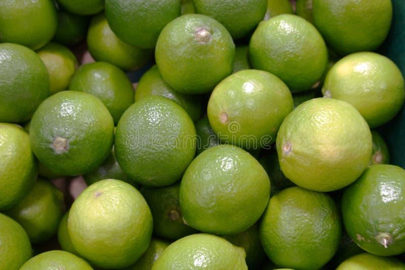 Stor hög av nya limefrukter som är till salu på specerihandlarna arkivfoton