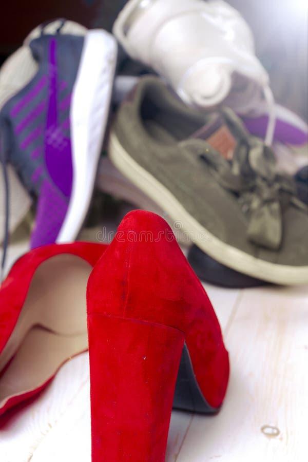 Stor hög av olika sportskor och röda för kvinna` s för hög häl skor på vit bakgrund arkivbild
