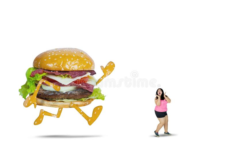 Stor hamburgare som jagar den feta kvinnan på studio arkivfoto