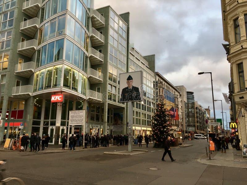 Stor julgran på berömda Checkpoint Charlie i Berlin royaltyfri foto
