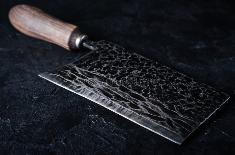 Stor köttköttyxa för tappning på mörk stenbakgrund tonad bild arkivfoto