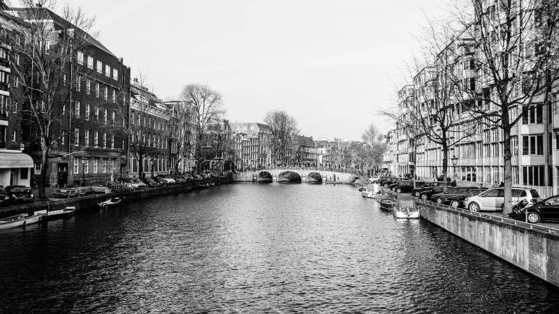 Stor kanal Singel i Amsterdam med bron i bakgrunden i svart & vitt arkivbilder