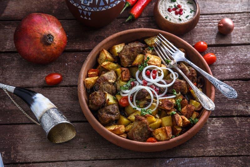Stor keramisk platta med grillade kött och potatisar med löken och vin Traditionell georgisk maträttojaxuri royaltyfri fotografi