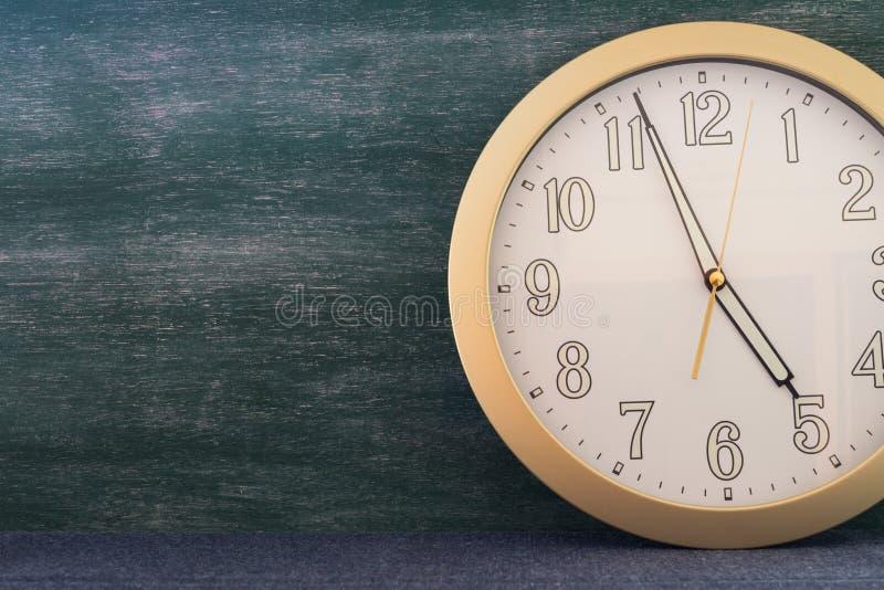 Stor klocka med svart tavlabakgrund arkivfoto