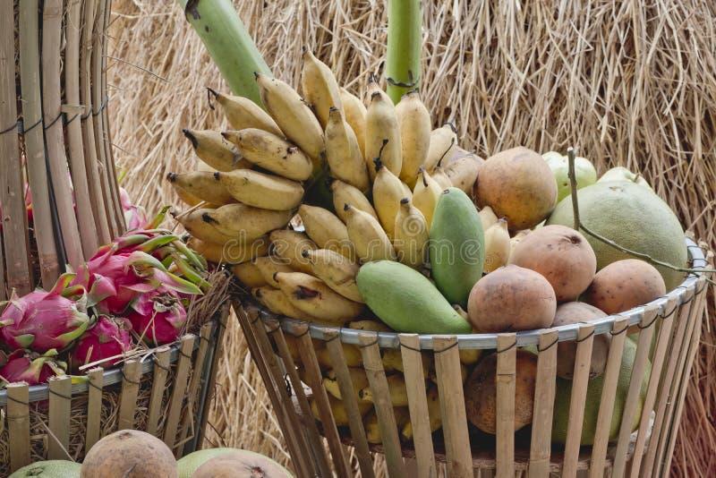 Stor korg med asiatiska nya frukter på bambubänk royaltyfria foton