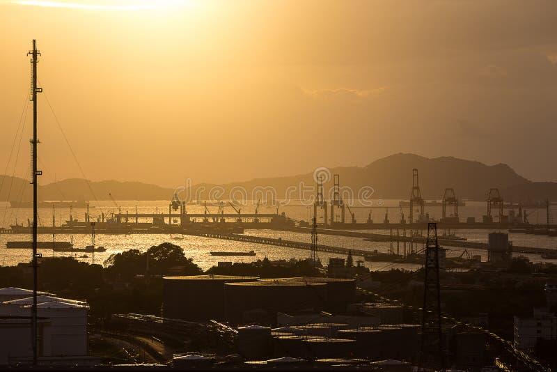 Stor kran i sändningsport i solnedgångtid arkivbild