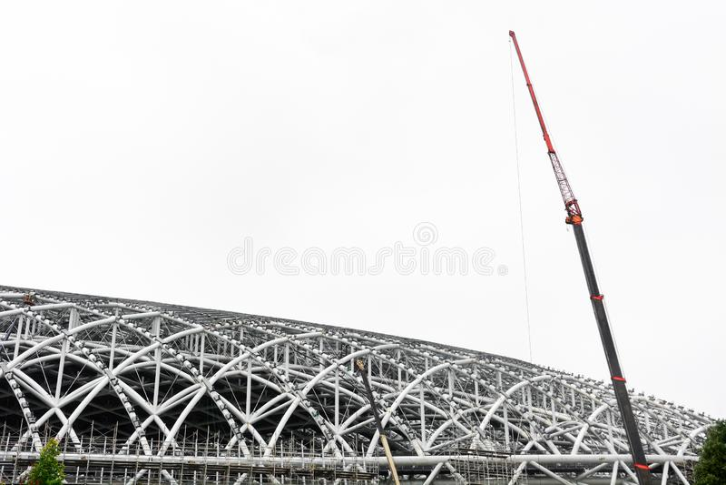 Stor kran på metallramen av stadiontaket, konstruktionen av den nya sportarenan som isoleras på vit bakgrund arkivfoto