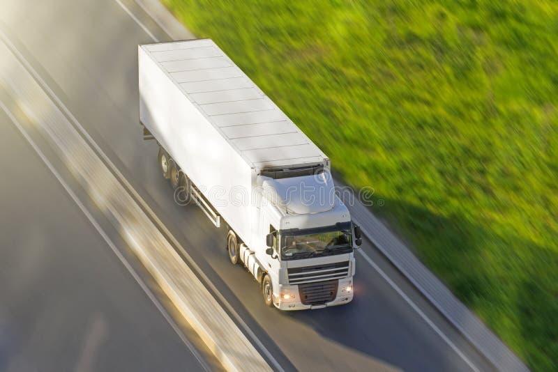 Stor lastbil med en släp på huvudvägen på en hastighet, som fortskrider asfalten, sikt från över royaltyfria bilder