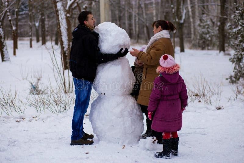 Stor lycklig familj: fadern, döttrar och farmodern hugger en stor verklig snögubbe royaltyfria foton