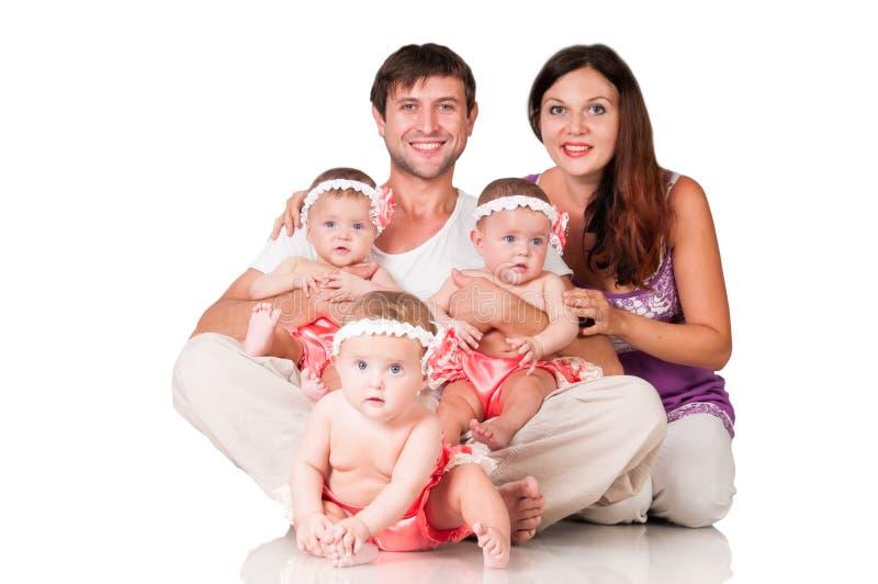 Stor lycklig familj med tre dottertrillingar arkivbild