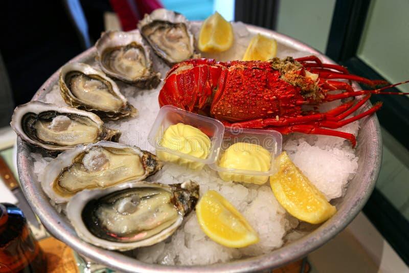 Stor maträtt med ny skaldjur, ostron med humret med citronen och sås på is royaltyfri fotografi
