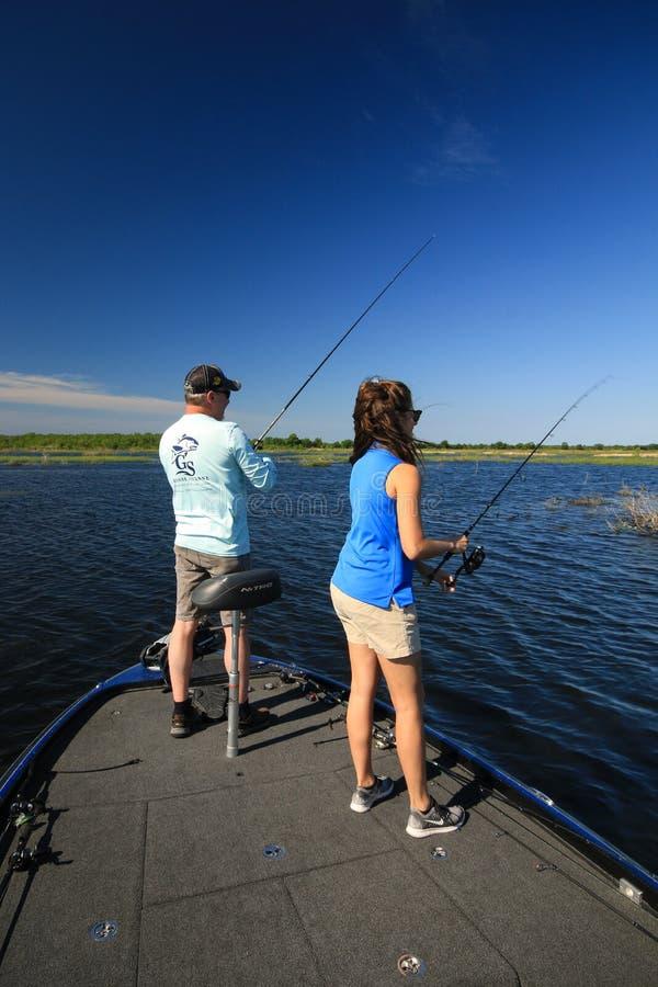 Stor mun Bass Fishing f?r man och f?r kvinna i fartyg royaltyfria foton