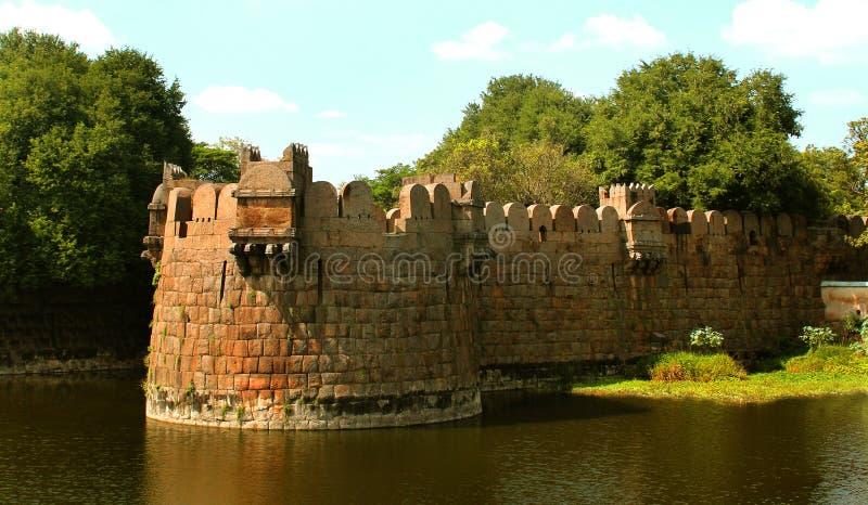 Stor mur med tinnar av vellorefortet med träd arkivfoton