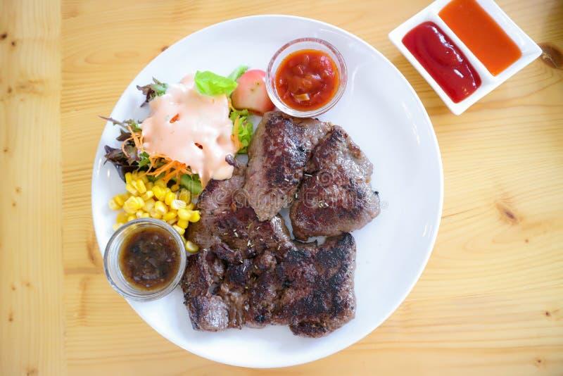 Stor nötköttbiff äter med grönsakhavresallad på en vit platta arkivfoton