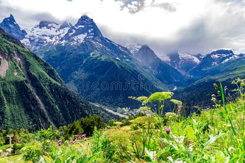Stor naturbergskedja Förbluffa perspektivet av det caucasian snöberget eller vulkan Elbrus med gröna fält som är blått arkivfoto