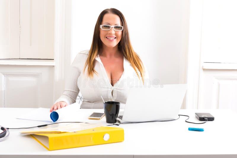 Stor och härlig sekreterare som arbetar i ett kontor royaltyfri foto