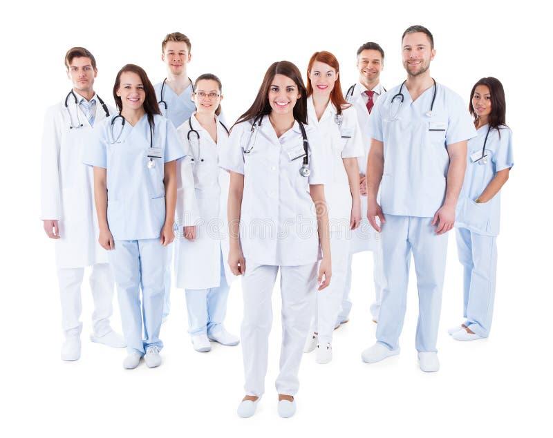 Stor olik grupp av den medicinska personalen i likformig arkivfoton