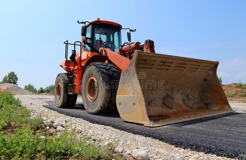Stor orange bulldozer på en halv stenlagd väg på konstruktionsplatsen arkivfoton