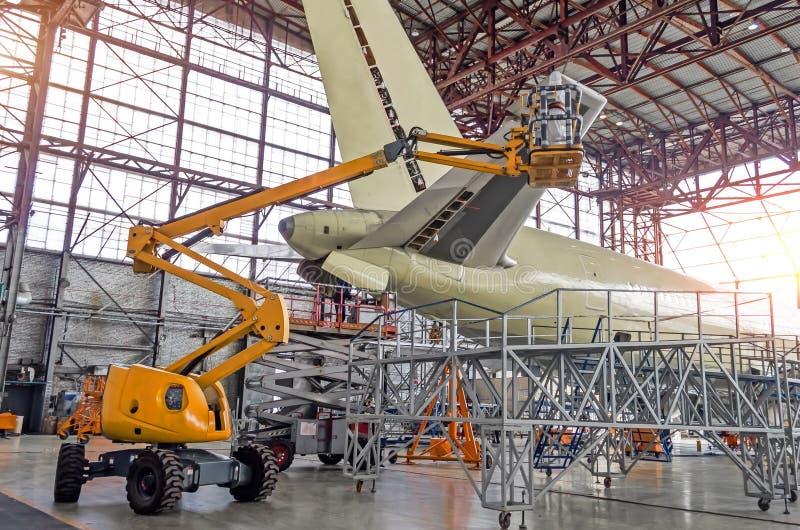 Stor passagerarflygplan på service i ett flyg inom den bakre sikten för hangar av svansen, på hjälpmaktenheten royaltyfria bilder