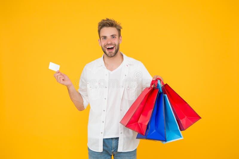 stor rabatt Stora köp för stora val Lycklig man som rymmer köp i pappers- påsar Gladlynt klientkund royaltyfri foto