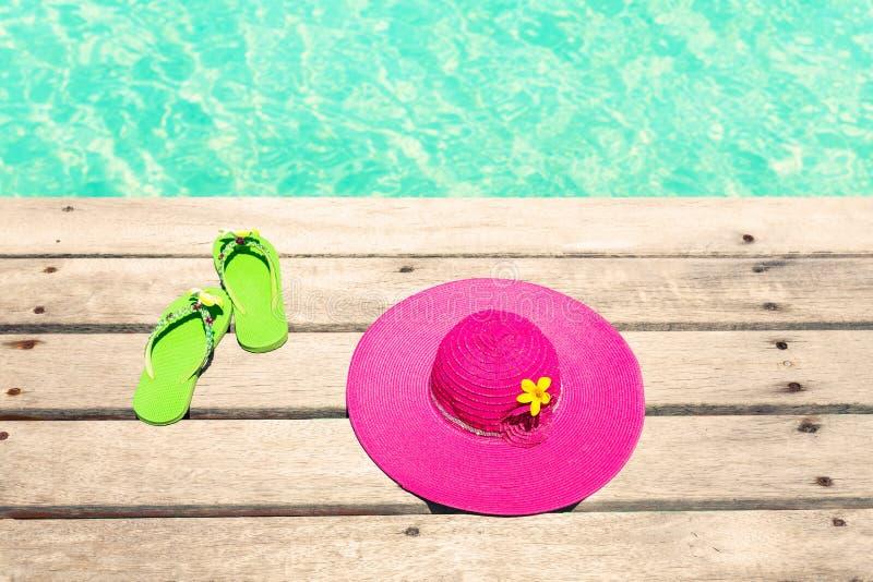 Stor rosa solhatt och sandal på trädäcket vid havet royaltyfria bilder