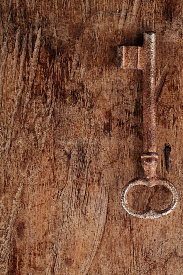 Stor rostig tappningmetalltangent på gammal träbakgrund royaltyfri foto