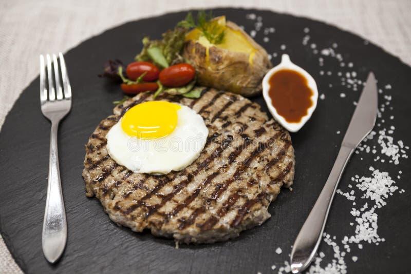 Stor, saftig läcker stek med ett stekt ägg och bakade potatisar på en stenplatta arkivfoto