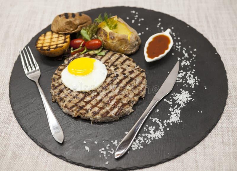 Stor, saftig läcker stek med ett stekt ägg och bakade potatisar på en stenplatta arkivbild