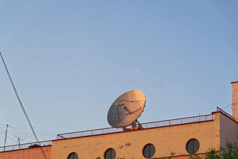 Stor satellit- maträtt för kommunikation på taket av en gammal industribyggnad arkivfoto