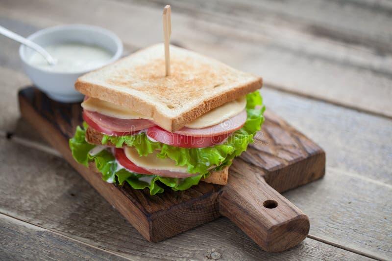 Stor smörgås för närbild med skinka, ost, tomater, sallad och vit sås på rostat bröd på en lantlig trätabell fotografering för bildbyråer