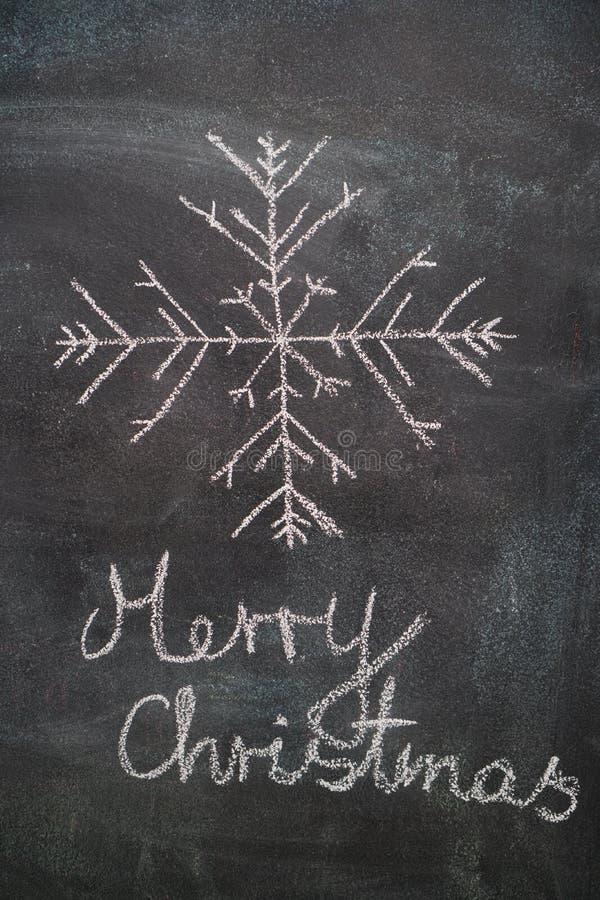 Stor snöflinga med glad jul som skriver på den svarta svart tavlan royaltyfria foton