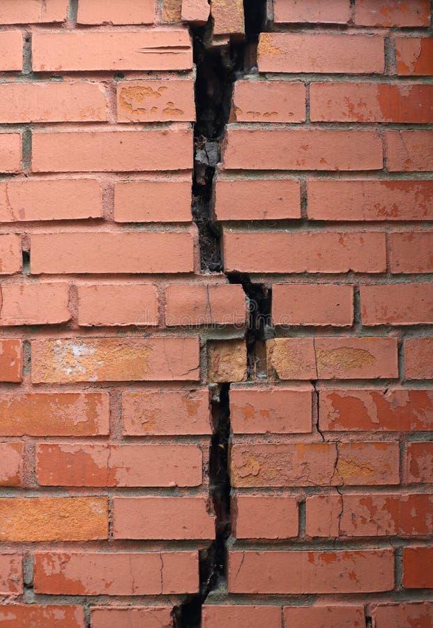 Stor spricka i väggen för röd tegelsten arkivfoto