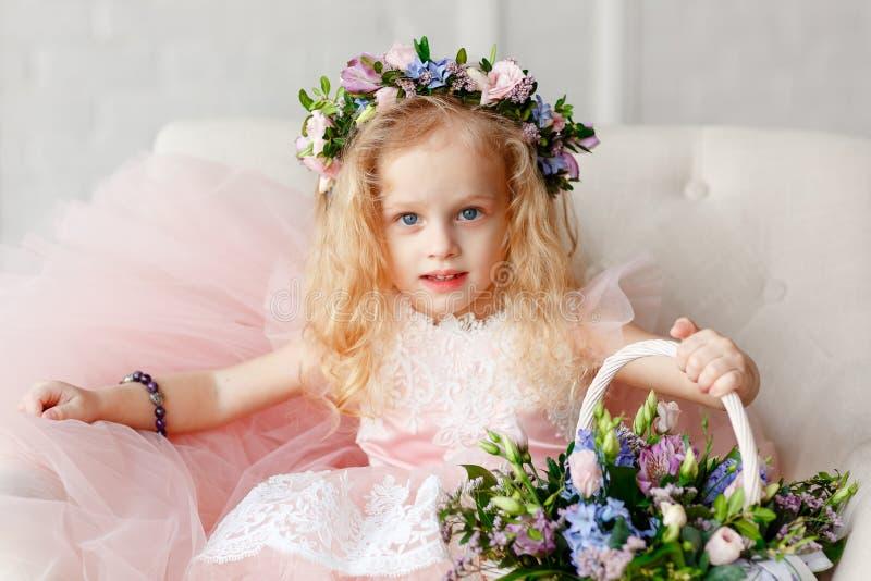 Stor stående av en gullig liten flicka i en krans av blommor och en härlig bukett av blommor i en ljus studio arkivbild